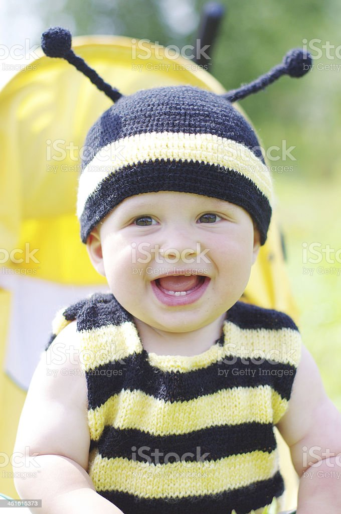 happy baby in bee costume sitting on baggy stock photo