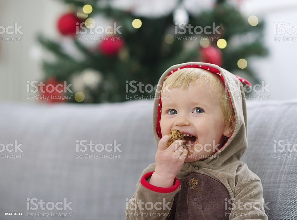 Happy baby in Christmas suit eating cookie royalty-free stock photo