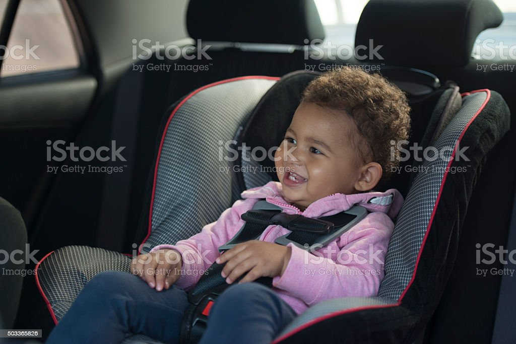 Happy baby in safety car chair. stock photo