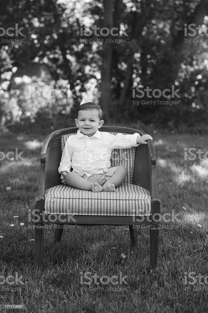 Happy Baby Sitting on Chair Outside royalty-free stock photo