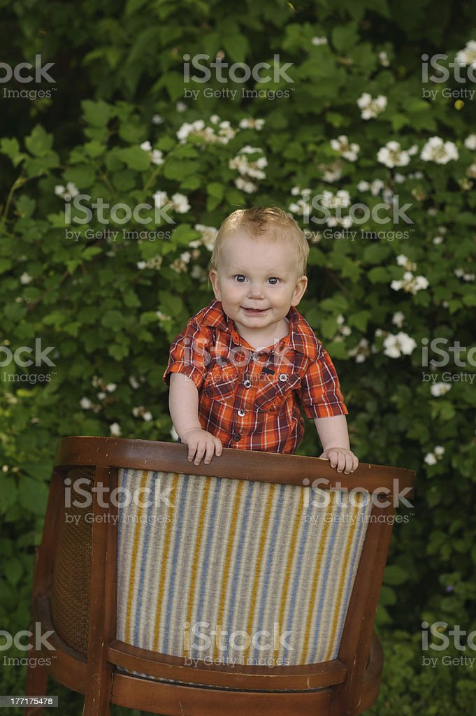 Happy Baby Standing on Chair Outside royalty-free stock photo