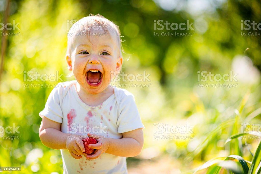 Happy baby with strawberry stock photo