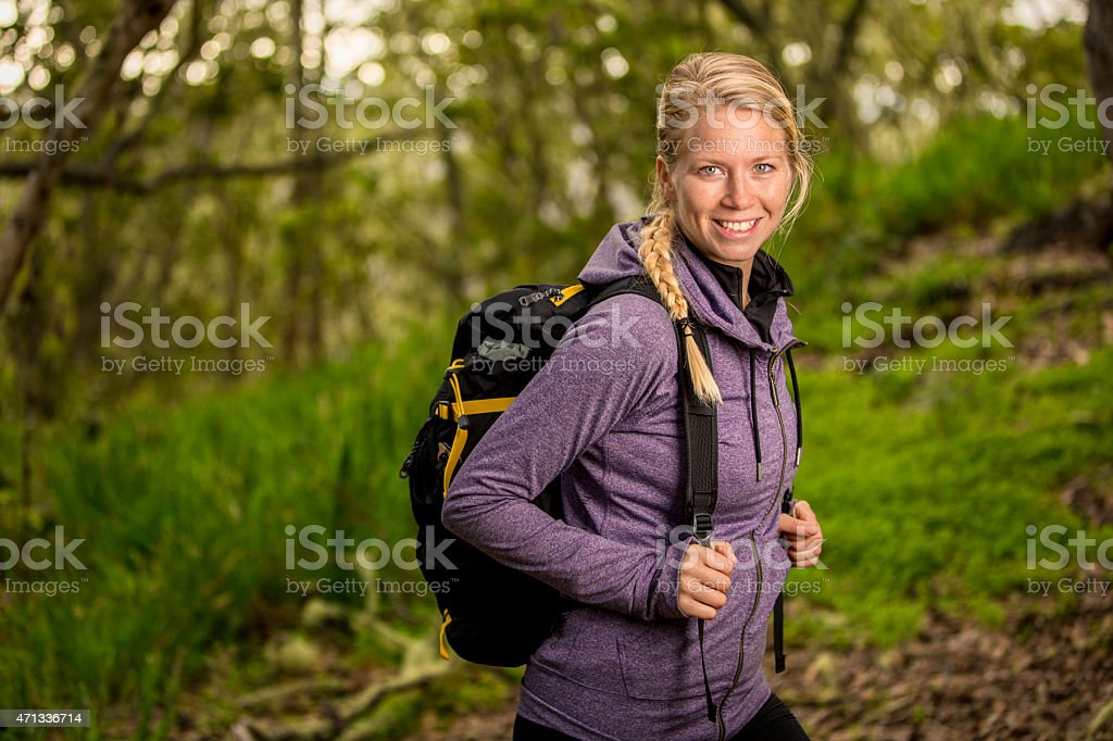 Happy Backpacking Woman Surrounded by Lush Green Forest stock photo