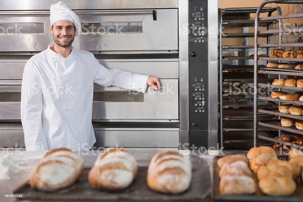 Happy baker leaning on professional oven behind bread loaves stock photo