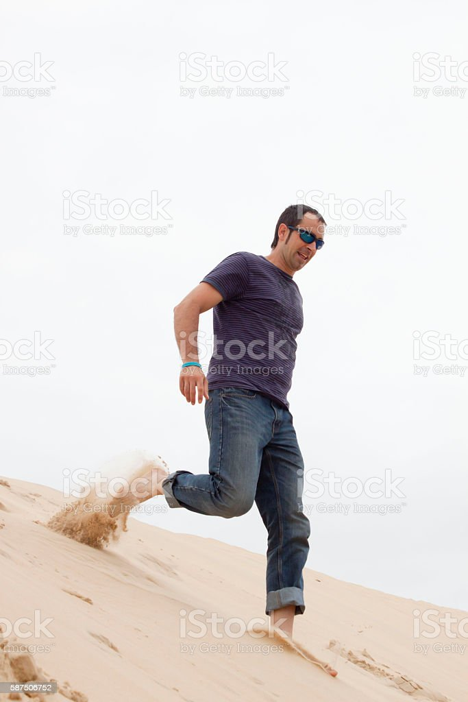 Happy barefoot man going down the Pilat dune in France stock photo