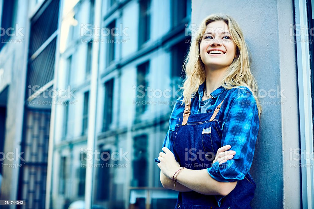 Happy barista standing arms crossed outside cafe stock photo