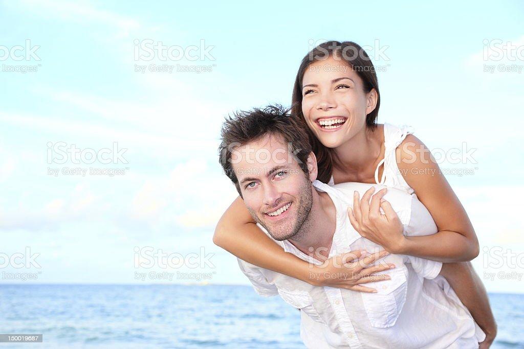 Happy beach couple piggyback royalty-free stock photo