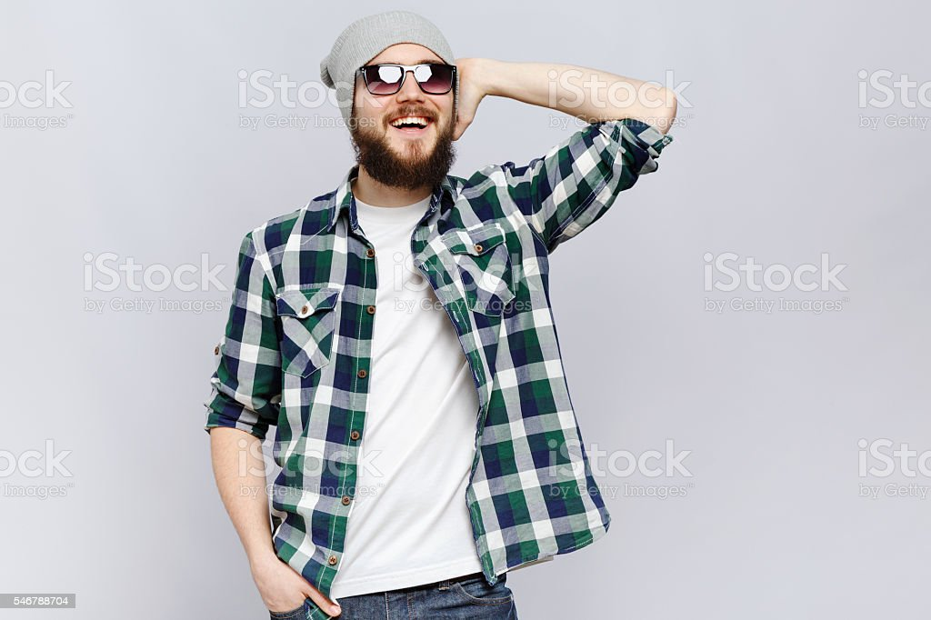 Happy bearded hipster posing on white background, in studio stock photo
