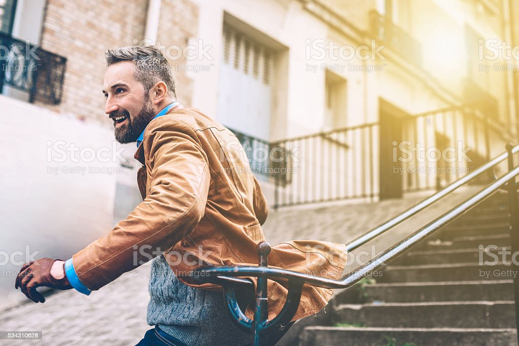 happy bearded man sliding down the balustrade of monmartre stairs stock photo