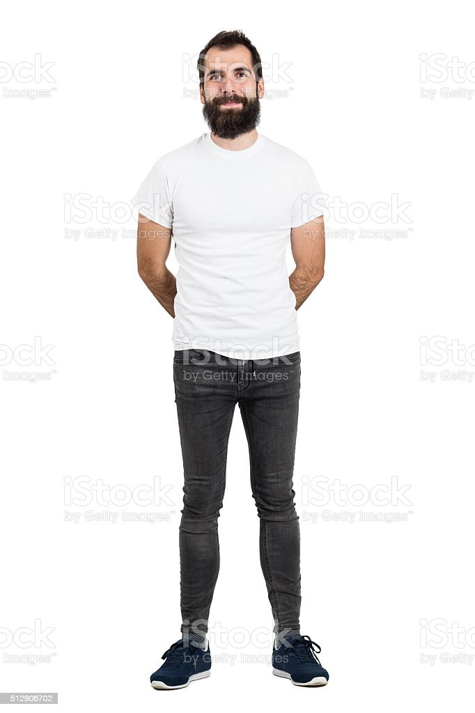 Happy bearded man with hands behind back in white t-shirt stock photo