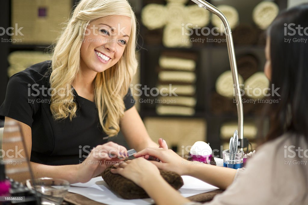 happy beautician giving a manicure royalty-free stock photo