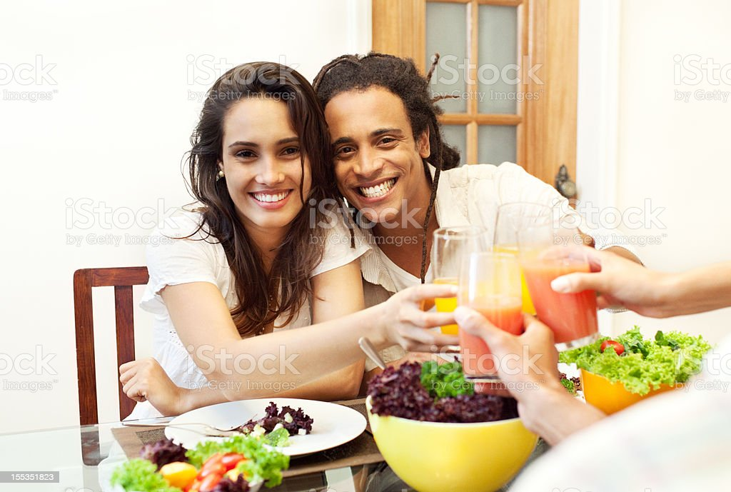 Happy beautiful brazilian couple having lunch at home with friends. royalty-free stock photo