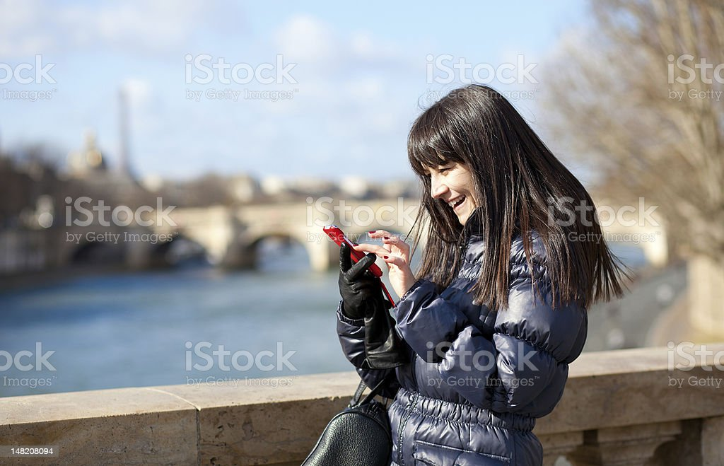 Happy beautiful brunette tourist in Paris sending an sms royalty-free stock photo