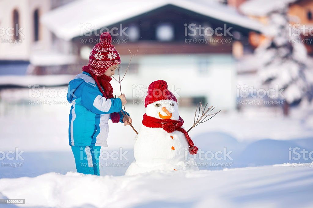Happy beautiful child building snowman in garden, winter stock photo