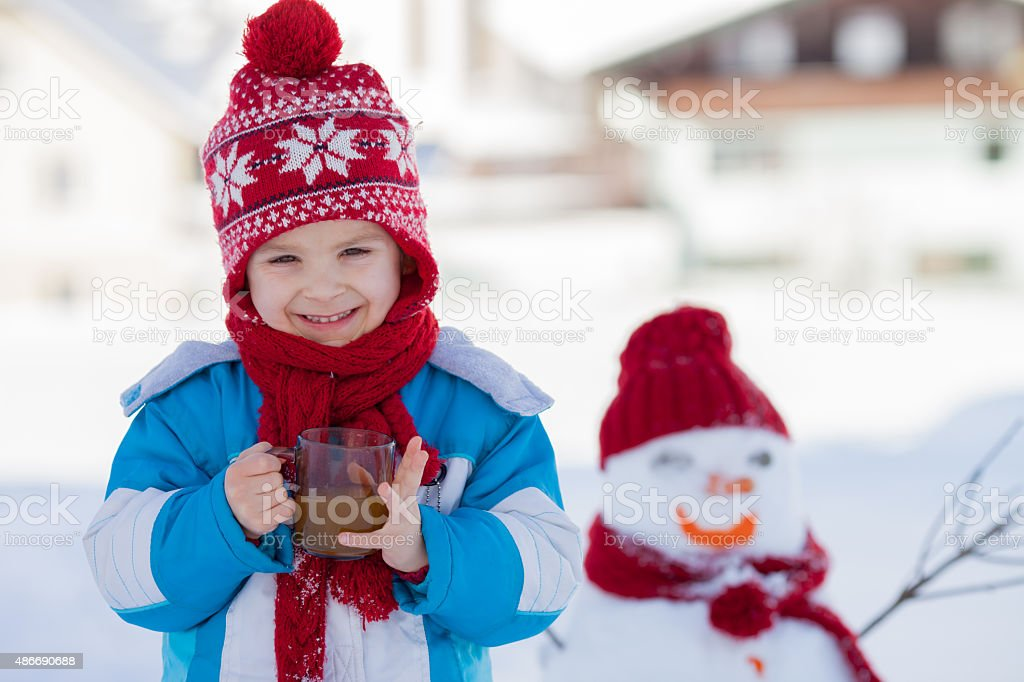 Happy beautiful child building snowman in garden, winter time, h stock photo