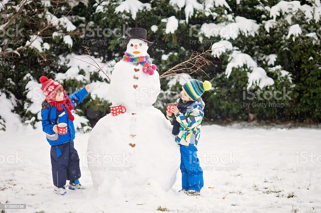 Happy beautiful children, brothers, building snowman in garden a stock photo