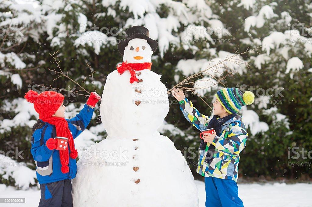 Happy beautiful children, brothers, building snowman in garden stock photo