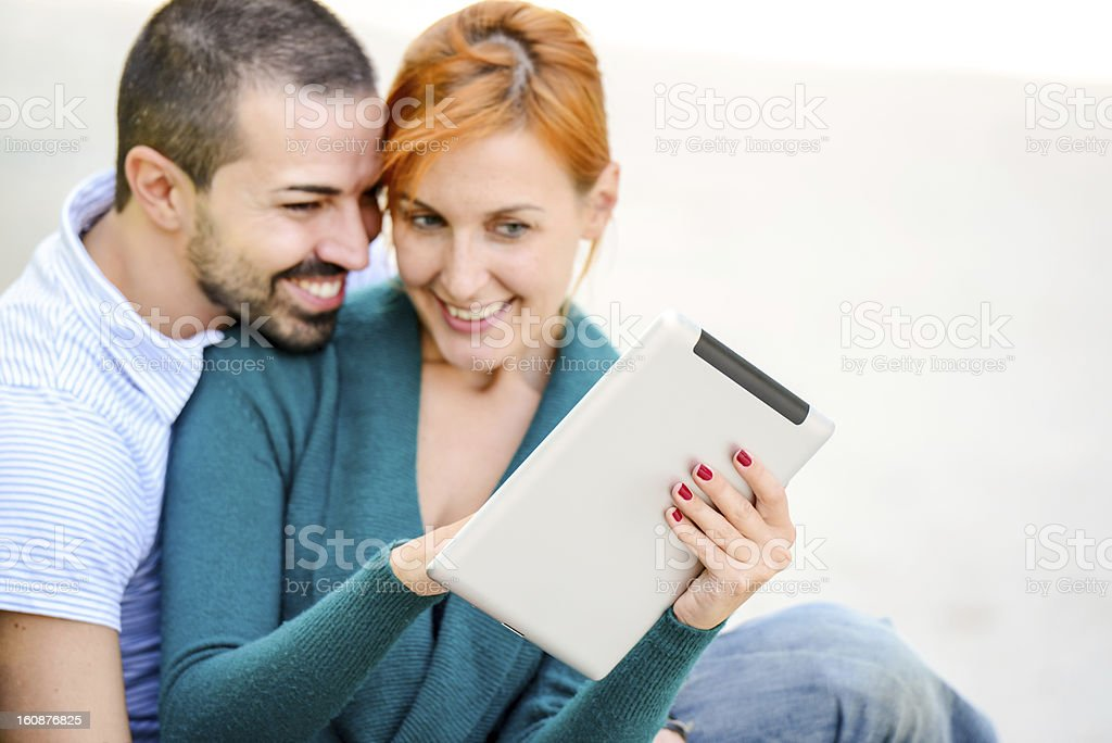 Happy Beautiful couple using Digital Tablet outdoors stock photo
