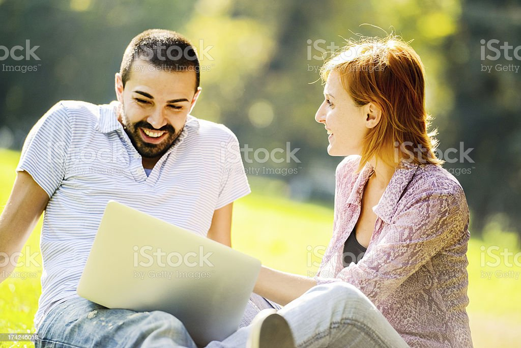 Happy Beautiful couple using Laptop outdoors stock photo