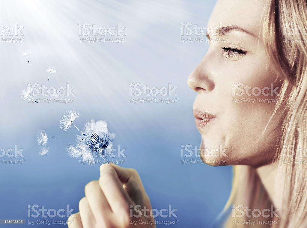 Happy beautiful girl blowing dandelion royalty-free stock photo