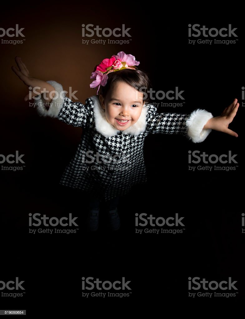 Happy beautiful little girl screaming with her hands up stock photo
