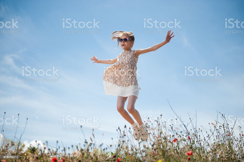happy beautiful little girl wearing sunglasses and dress jumping outdoors stock photo
