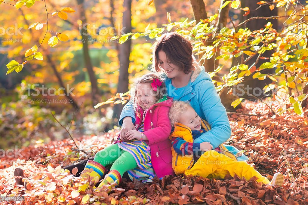 Happy beautiful mother and adorable kids in autumn park stock photo