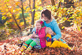 Happy beautiful mother and adorable kids in autumn park