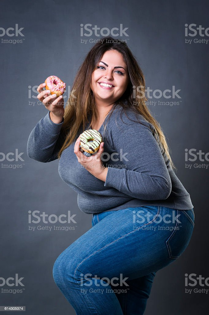 Happy beautiful plus size model in jeans posing with donuts stock photo