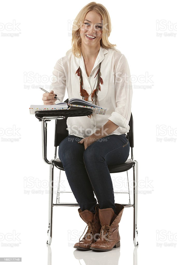 Happy beautiful woman sitting on a writing chair stock photo