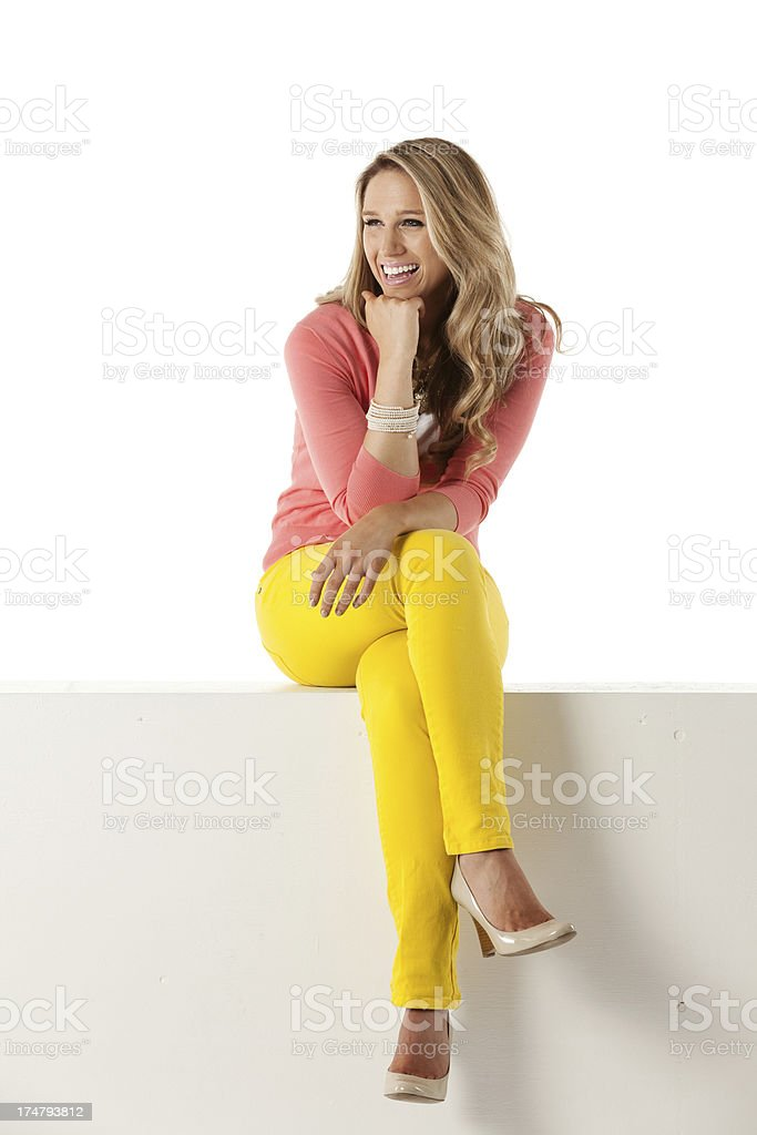 Happy beautiful woman sitting on the ledge of a wall royalty-free stock photo