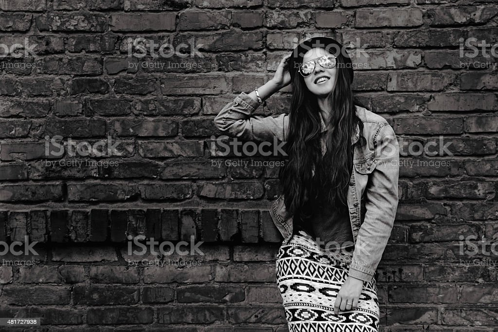 Happy beautiful woman stands near the old brick wall. royalty-free stock photo