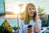 Happy beautiful woman walking and talking with smart-phone