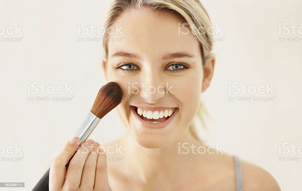 Happy beautiful young lady applying makeup royalty-free stock photo