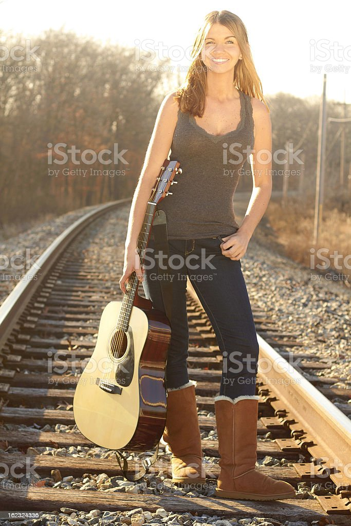 Happy Beautiful Young Lady Holding Guitar On Railroad Tracks royalty-free stock photo