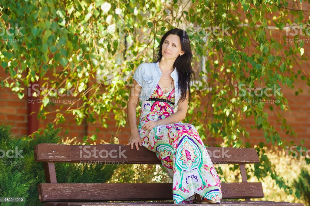 Happy beautiful young woman sitting on a bench near the tree stock photo