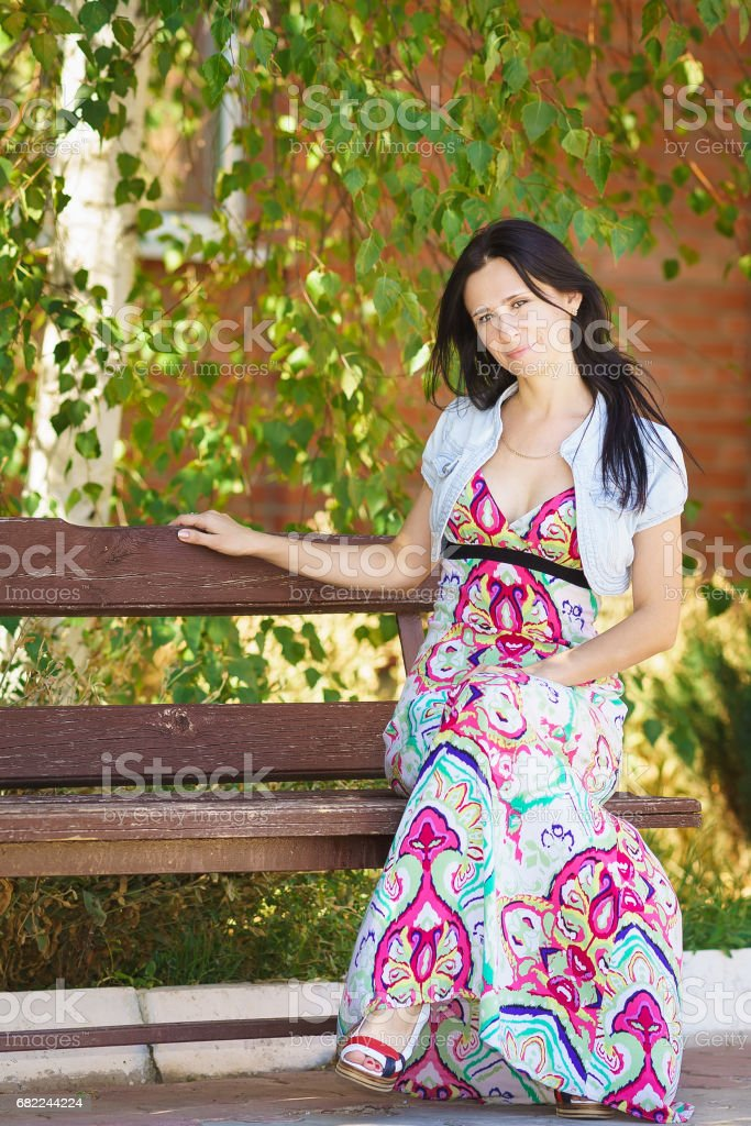 Happy beautiful young woman sitting on a Park bench stock photo