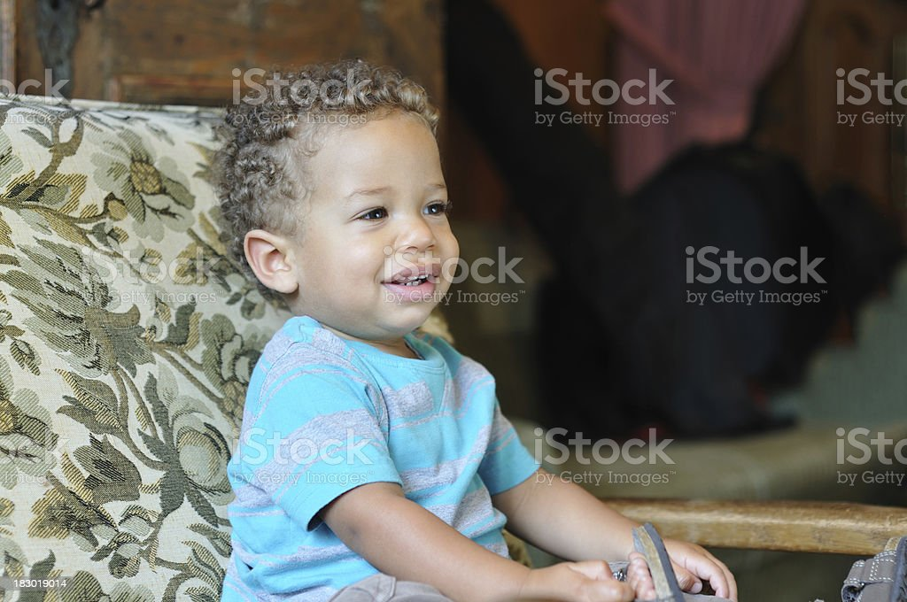 happy bi-racial baby sitting on chair stock photo