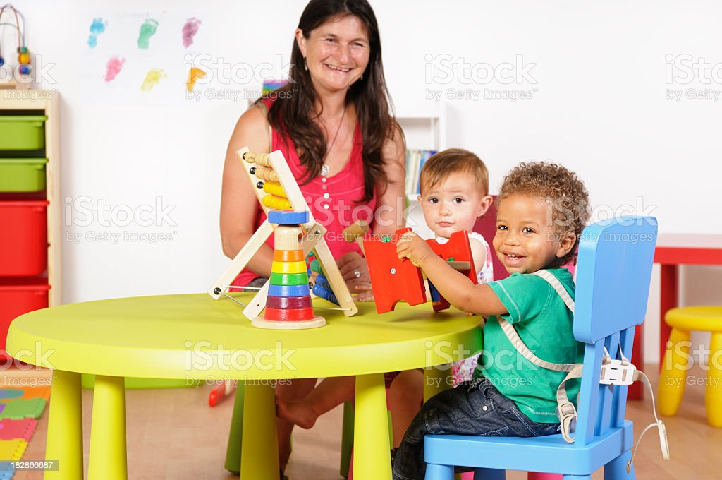 Happy Biracial Baby/ Toddler Enjoying Playtime In A Nursery Setting royalty-free stock photo