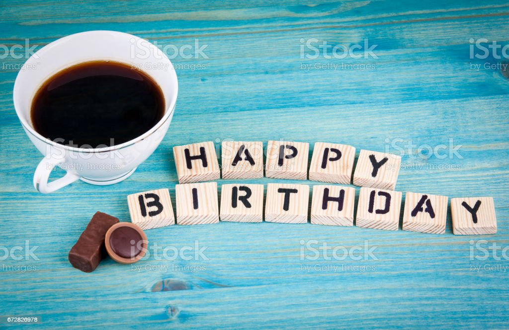 happy birthday. Coffee mug and wooden letters on wooden background stock photo