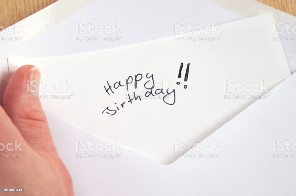 Happy Birthday, hand holding handwritten letter in white envelope, wooden background stock photo