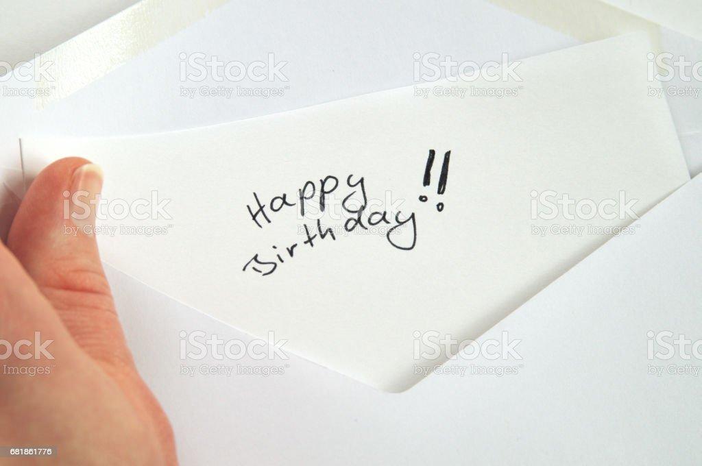 Happy Birthday, hand holding handwritten letter in white envelope stock photo