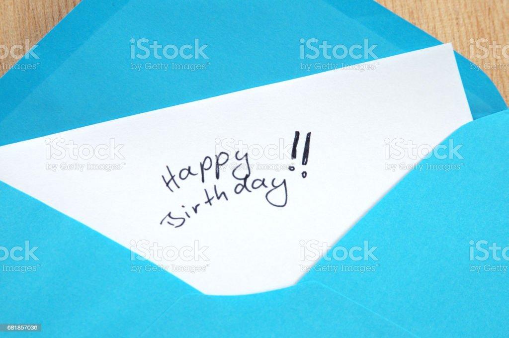 Happy Birthday, handwritten letter in blue envelope, wooden background stock photo