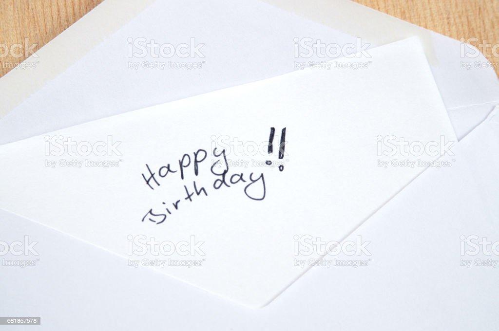 Happy Birthday, handwritten letter in white envelope, wooden background stock photo