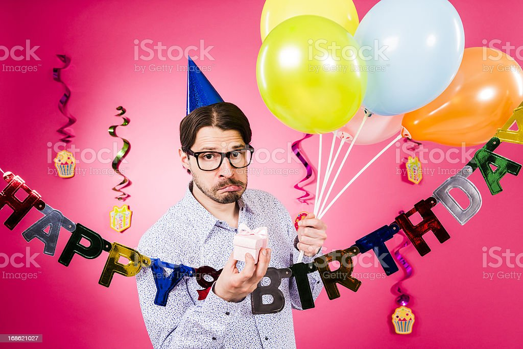 Happy birthday, Nerdy man making faces, holding gift, multicolored balloons royalty-free stock photo