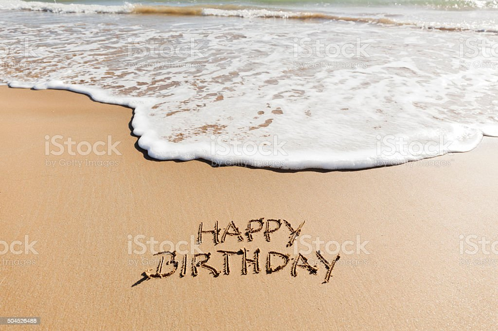 Happy Birthday written in the sand on a beach. stock photo