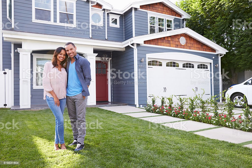 Happy black couple standing outside their house stock photo