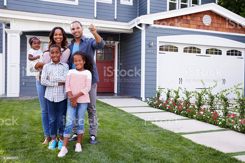 Happy black family standing outside their house, dad stock photo
