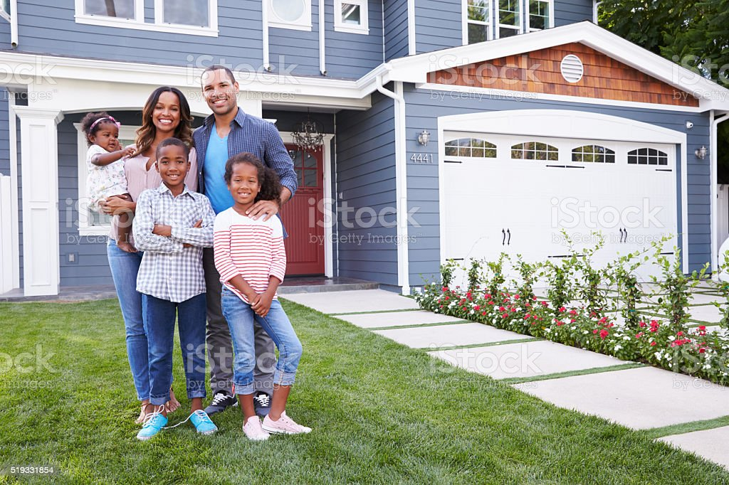 Happy black family standing outside their house stock photo