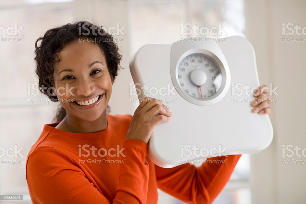 Happy Black woman holding scale stock photo